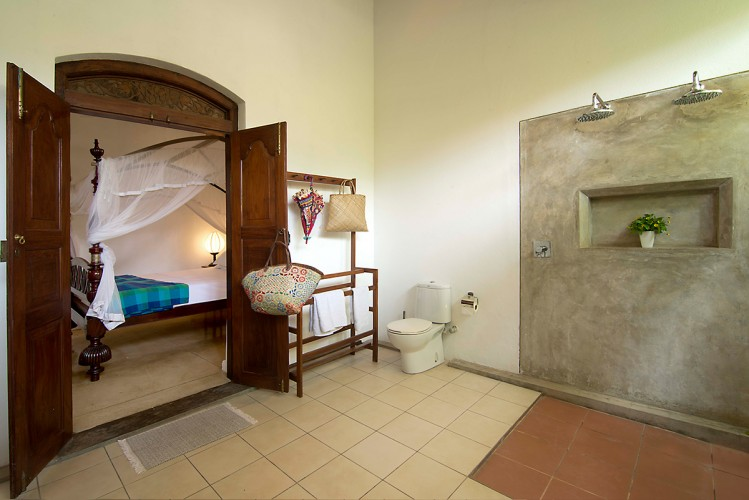 Coconut Grove Villa's bathroom against the mahogany bed, decked in net curtains