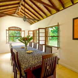 High vaulted timber ceilings combine into a cool dining room space at Coconut Grove Villa