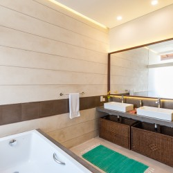 Serendipity Villa bathrooms use of opaque glass bath screens draw the light reflected on Koggala lake into each one.
