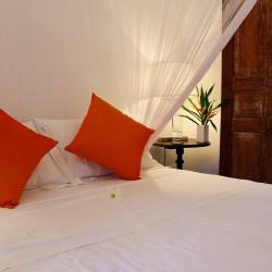 Lassana Kanda Villa Bedroom style; orange pillows on crisp white sheets