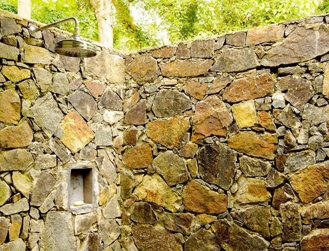Outdoor showers are contained within natural stone walls at Ivory House