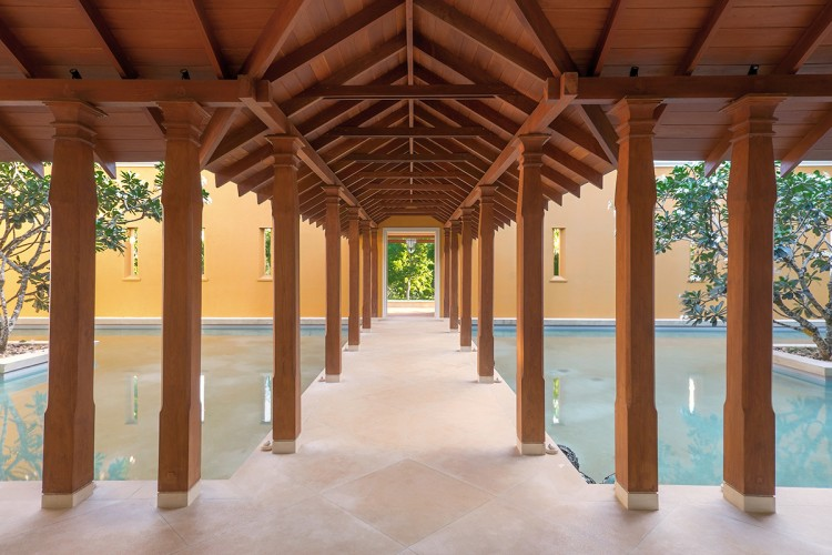 Rich honey coloured timber support the structure over the walkway over the Ranawara Beach Villa central pond