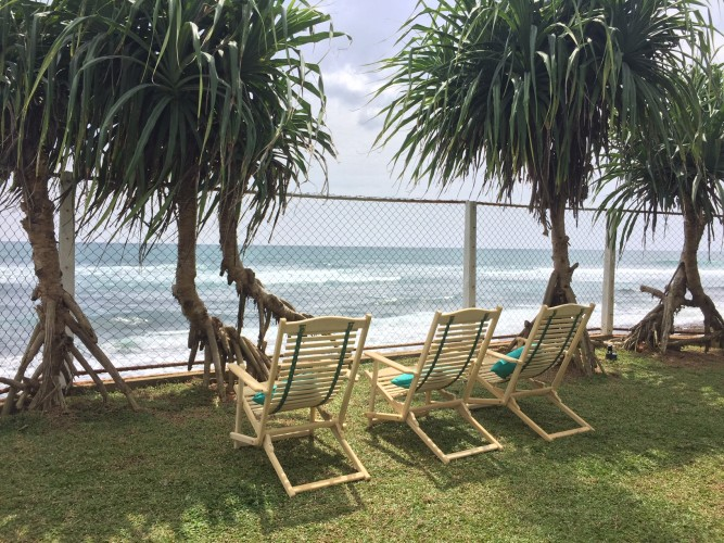 A shady break in the deck chairs overlooking the beach and surf at Reef House Beach Villa