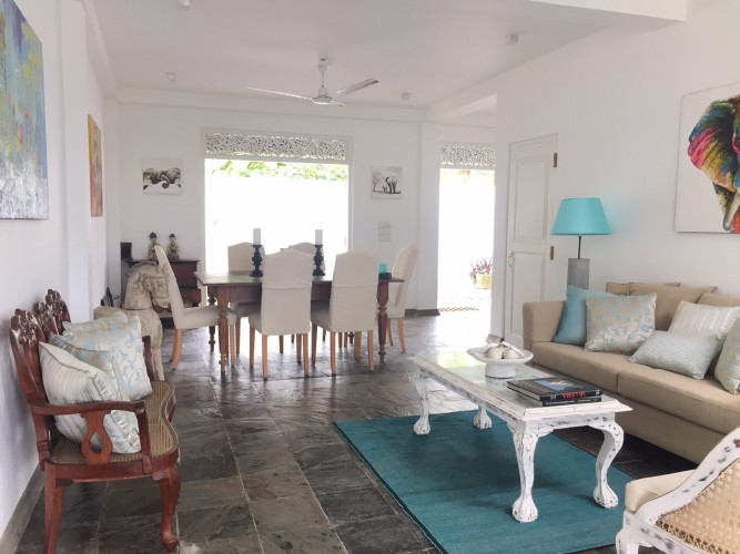 Reef House Beach Villa's stone floors blend well with the lounge and timber furninture
