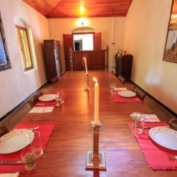 Somaland Estate Bungalow dining room features a handmade timber table surrounded by antique furnishings