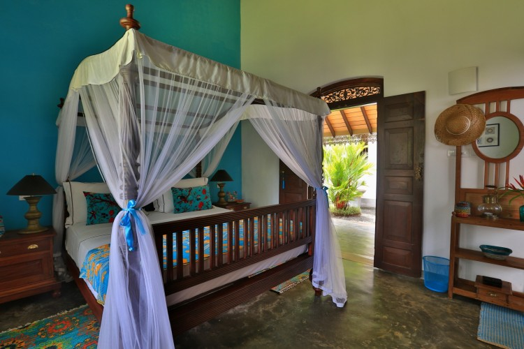 Villa Sepalika Unawatuna separates rooms with colour like the turquoise feature wall behind this king sized four poster bed