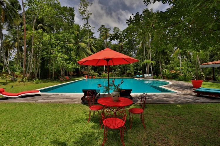 Villa Sepalika Unawatuna uses burnt orange umbrellas and lounge covers to catch your eye around the pool