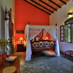 Villa Sepalika Unawatuna third king sized suite featured colour is burnt orange which makes the furniture and traditional carved windows 'pop' off the background