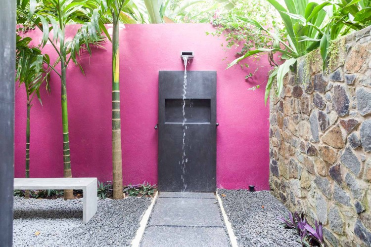 Modern Luxury in the stylish outdoor shower. Bright pink, natrual stone, polished cement and large paving stones at Villa Wambatu