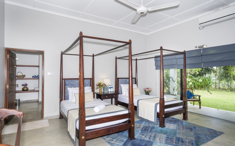 Villa Ronnaduwa one suite features twin single four-poster beds with direct garden access through French doors